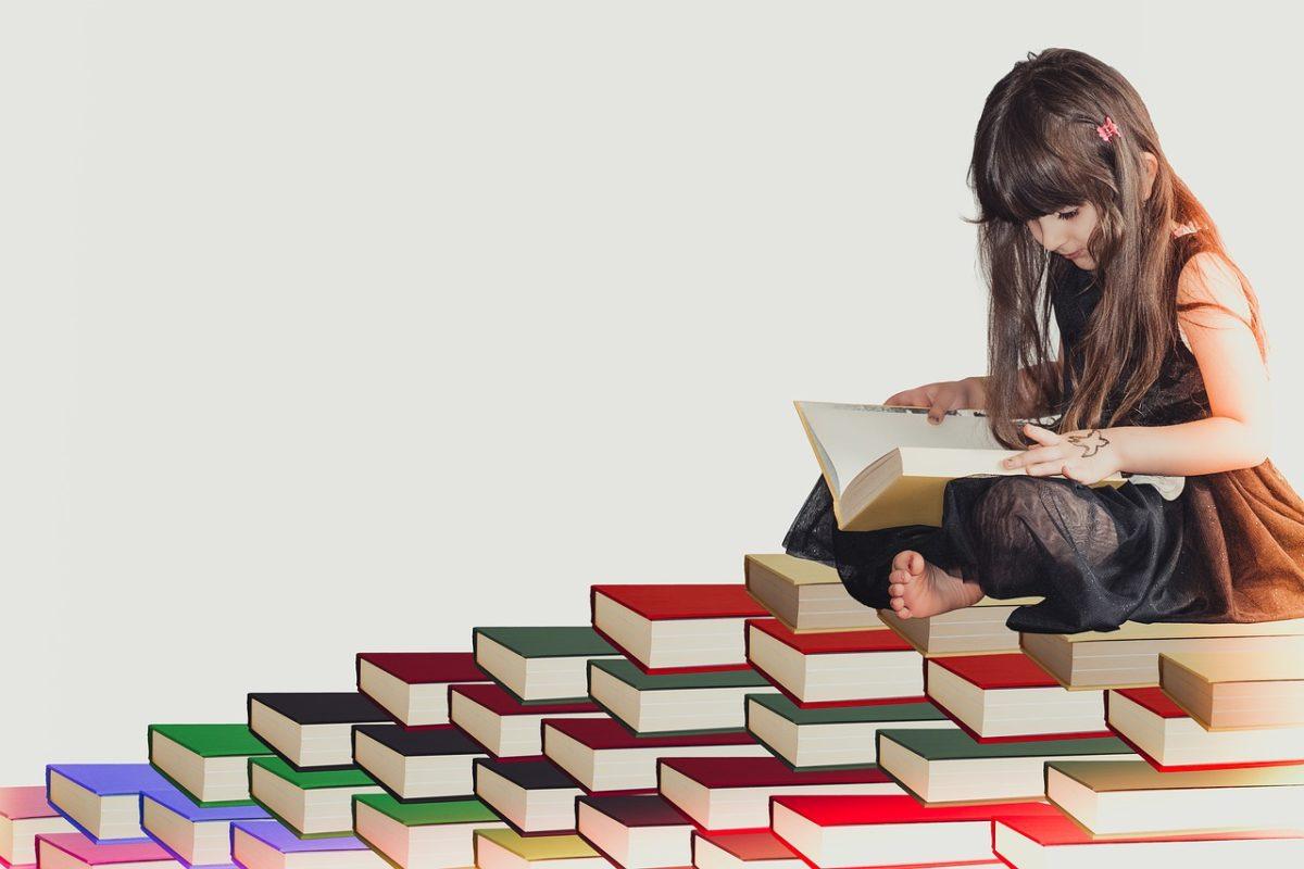 本の上で本を読む女の子