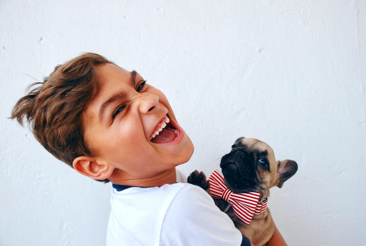 笑顔で犬を抱いている少年