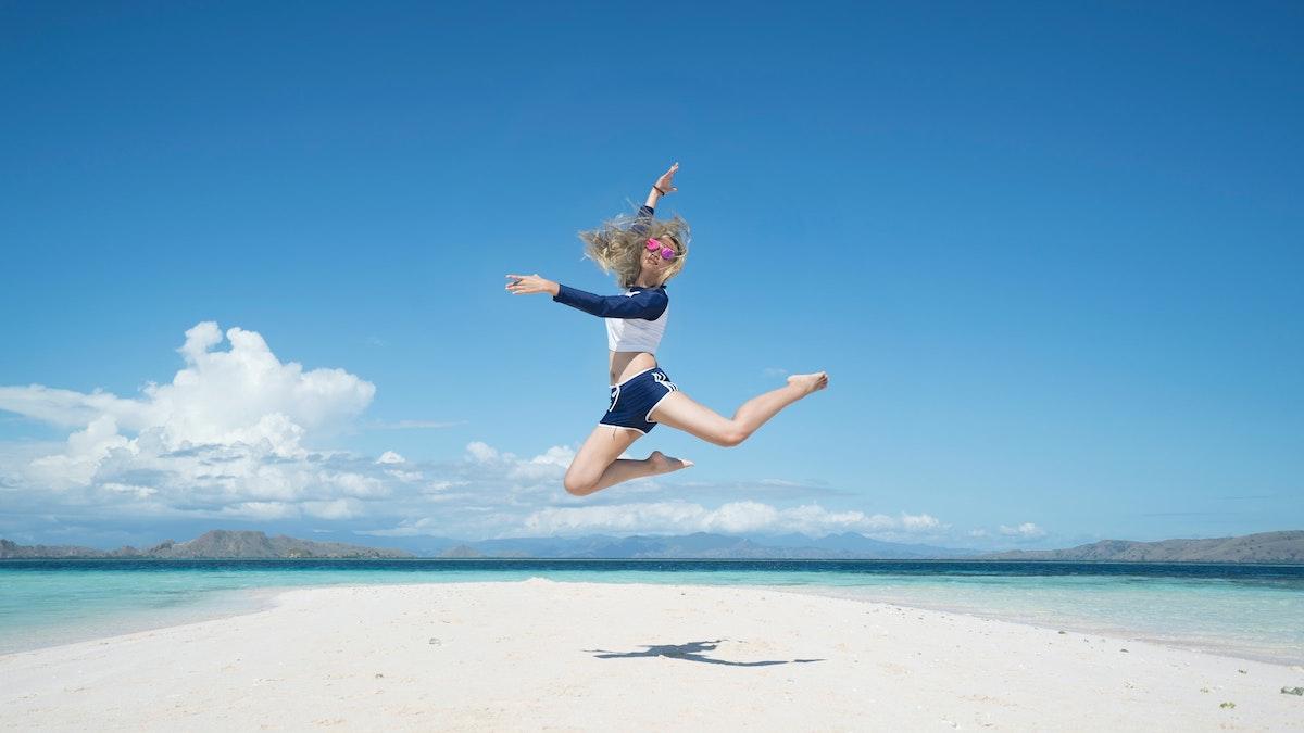 海の砂浜ででジャンプする女の子