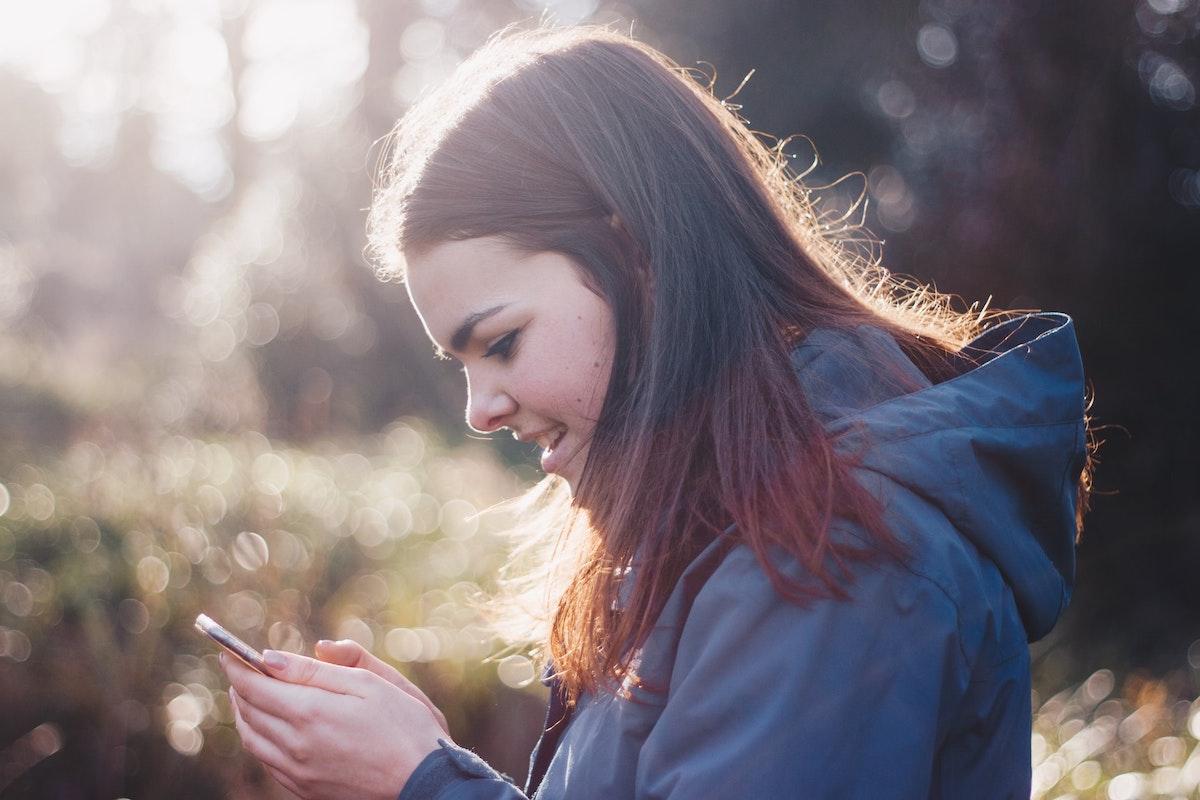 スマホでSNSを見て笑っている女の子