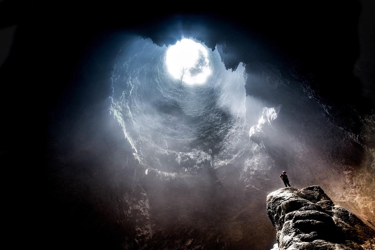 洞窟で出口を見上げる少年