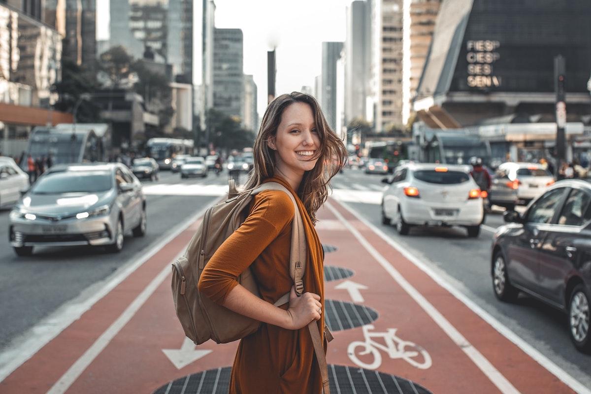 道路の真ん中を笑顔で歩く女性