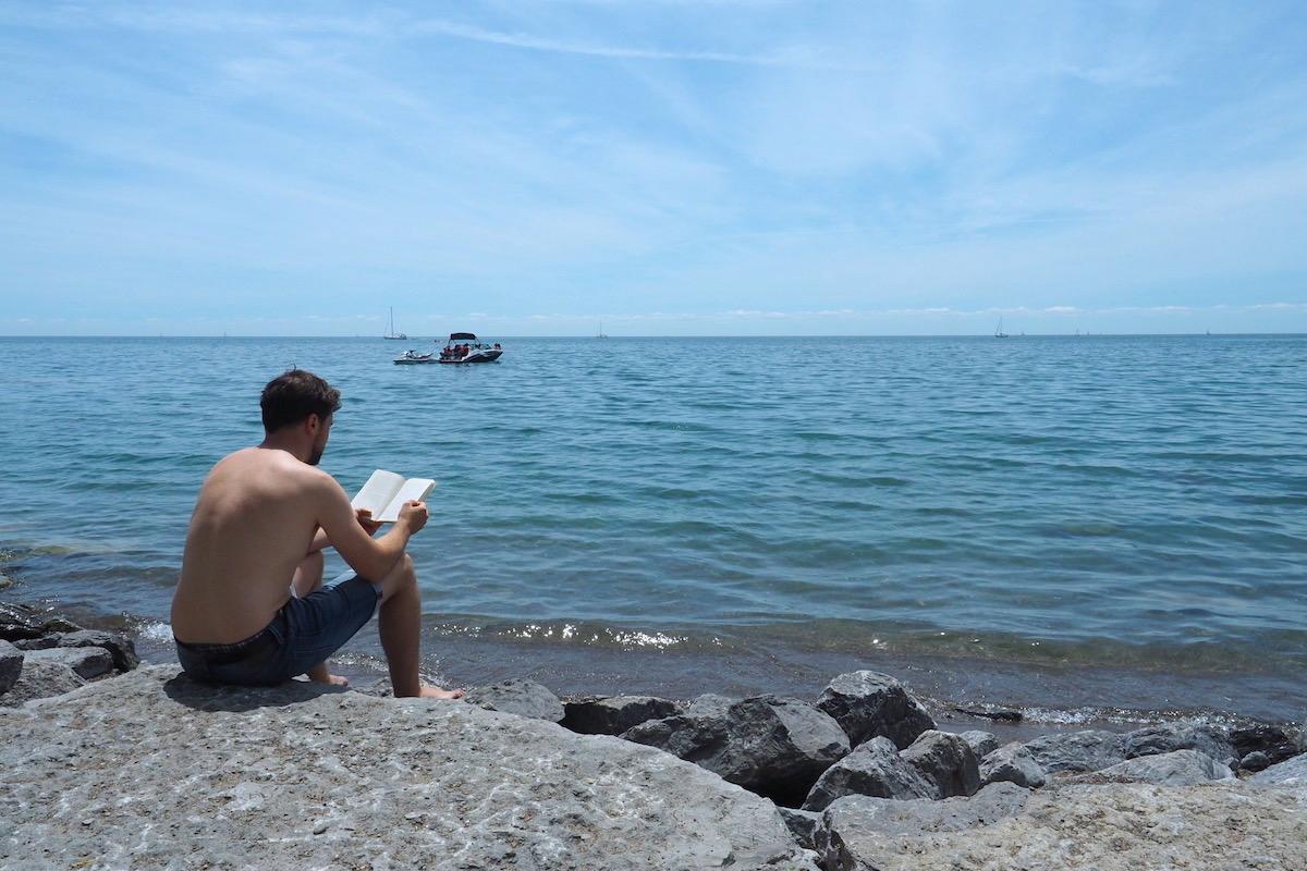 トロントのウッドバイン・ビーチで本を読む男性