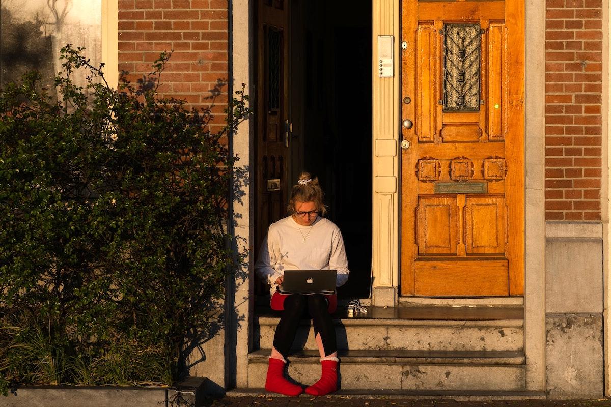 オンライン作業を玄関でする女性