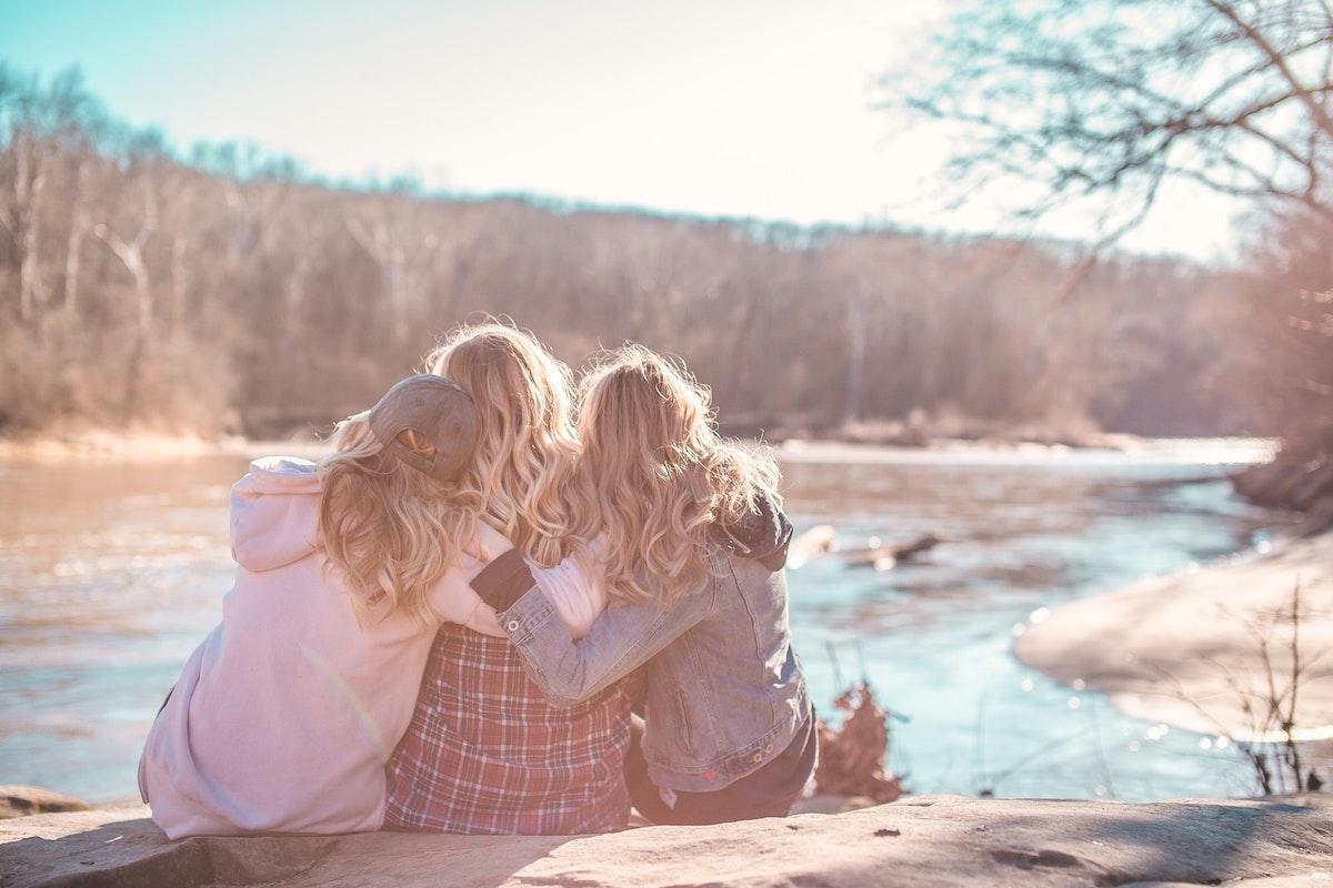海辺で肩を寄せ合う女性3人
