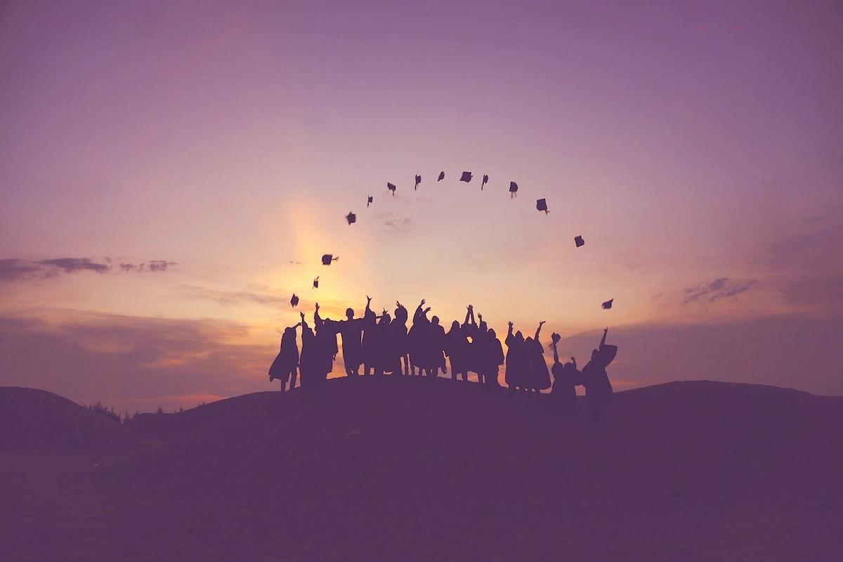 卒業生が帽子を空に飛ばしている