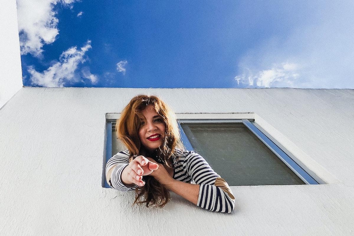 窓から手を差し伸べる女性