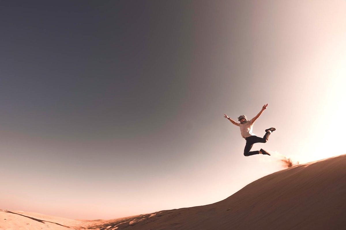 砂漠でジャンプをする人